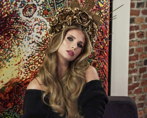 Modelka ze zdobieniem na głowie prezentuje makijaż dzienny na tle obrazu w galerii w mieście Tychy
