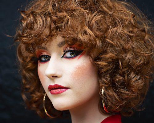 Makijaż artystyczny wykonany przez mobilną wizażystkę na modelce w kręconych włosach w mieście Katowice